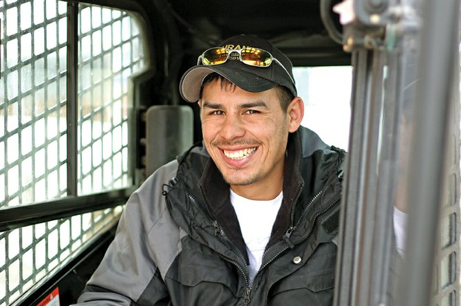 Eric Duran sits Friday in a skid steer vehicle that belongs to his family's painting business. Duran is a Craig resident who has worked with his father, Leo, since he was 12.