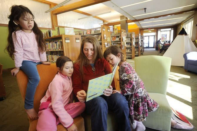 Jessica Yamashita reads to her daughters, from left, Madelyn, 6, Julia, 8, and Lillian, 4, on Wednesday at Bud Werner Memorial Library. Jessica Yamashita moved to Steamboat from California in May with her husband Brent. The city's population grew from 9,815 in 2000 to 12,088 in 2010, according to figures released Wednesday.