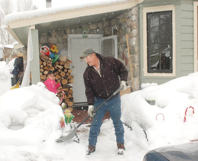 Evelyn Tarango watches her grandfather, Silvino Cano, shovel snow outside the family home in Sleepy Bear Mobile Home Park on Friday. The mobile home park is listed for sale for $3.2 million.