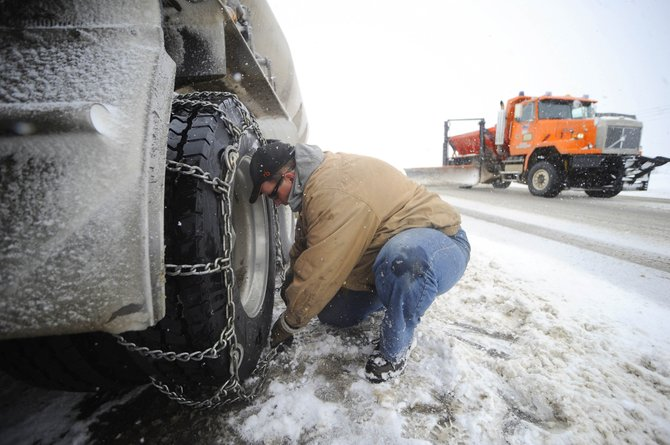 Mike Austin, of Loveland, chains up his truck along U.S. Highway 40 before ascending Rabbit Ears Pass on Friday morning.