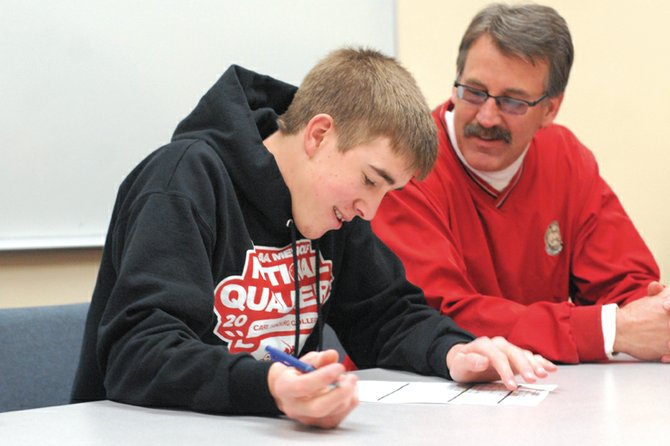Mark Dockstader, left, looks over his letter of intent to play golf at Carlsandburg College in Galesburg, Ill., this fall with his dad, Tom Dockstader, Feb. 23 at Moffat County High School. The MCHS senior missed most of his senior season due to a shoulder injury and said a junior college is the best place for him to start at.