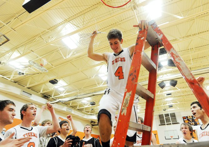 Hayden senior Graig Medvesk climbs down after cutting down the net following his team's 58-56 district championship victory against Paonia. Medvesk scored with 4 seconds remaining to give his team the win.
