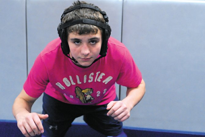 TJ Shelton, 12, poses in his starting wrestling stance Feb. 22 in the Moffat County High School wrestling room. With victories next month in Rocky Mountain National tournaments in Arizona and Denver, Shelton can win the Triple Crown, the Tri-State belt, the Golden Gear and the World Championship belt.