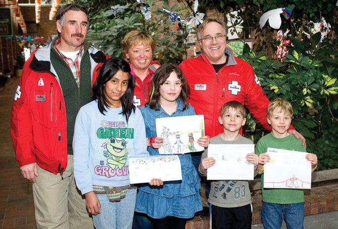 Ski Patrol members Scott Ciufo, from left, Michele Baxter and John Kohnke visit Strawberry Park Elementary School on Thursday afternoon to hand out the awards for the annual ski safety poster contest. Winners include second-place Maria Santiago, winner Sarah Heineke and third-place Logan Speigel and Colin Kagan.