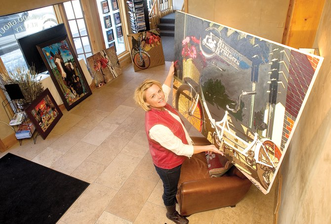Local artist Michelle Ideus hangs her work at the Colorado Group Realty office in downtown Steamboat Springs on Wednesday afternoon.