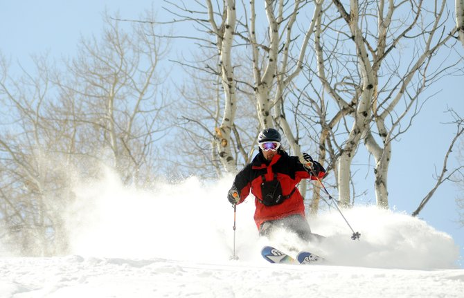 Three Forks Ranch guide Jason Neiberger skis down a run through the powder on Three Forks Mountain, which overlooks the ranch's guest lodge. The resort expanded its winter offerings this year to include private snowcat-accessed skiing and snowboarding.