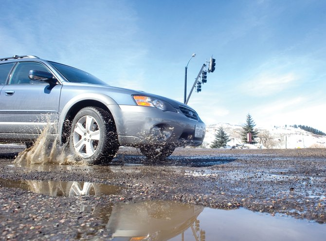A Subaru wagon hits a pothole as it turns off U.S. Highway 40 onto Hilltop Parkway on Monday morning. Road crews are making temporary fixes to potholes, but permanent repairs will have to wait for warmer weather in spring and summer.