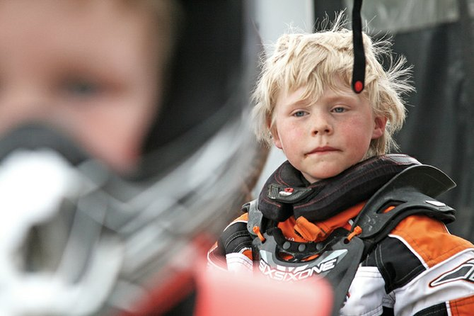 Logan Montgomery, 7, of Moffat County, relaxes after a snocross race last month at Wyman Museum in Craig. Logan, who races in Xtreme Mountain Racing's 120 class, entered competition midseason this year. He had been recovering from an August 2010 dirt bike accident that left him with a broken femur. Logan's brother, Luke, 4, is also shown above.