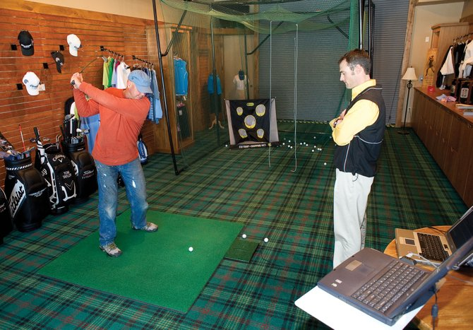 Golfer Tim Tilton works with Luke Brosterhous, director of instruction at Haymaker Golf Course, on Thursday morning inside the proshop at Haymaker Golf Course. Brosterhous uses a simulator to teach golfers throughout winter.