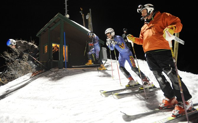 A line of skiers waits for their turn Thursday during the final Town Challenge slalom race of the season. The skiers are competitive, many wearing race suits and buying special equipment. A light-hearted atmosphere dominates the events, however.