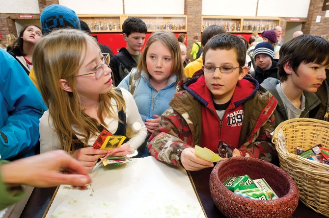 Steamboat Springs Middle School students, from left, Brittney Brown, Zoe Kirchner and Eric Kerbs wait for their turns at the middle school store Wednesday. Students can trade Know the Code cards for candy, toys and pizza. The cards are handed out as a reward for good behavior.