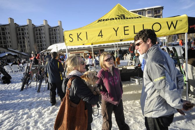 Two-time Olympian Caroline Lalive, left, visits with Ski 4 Yellow co-chairman Kerry Shea and his wife, Jennifer, during a sign-up event Thursday at Slopeside Grill. About 70 spots remain for the cancer fundraiser March 25 and 26.