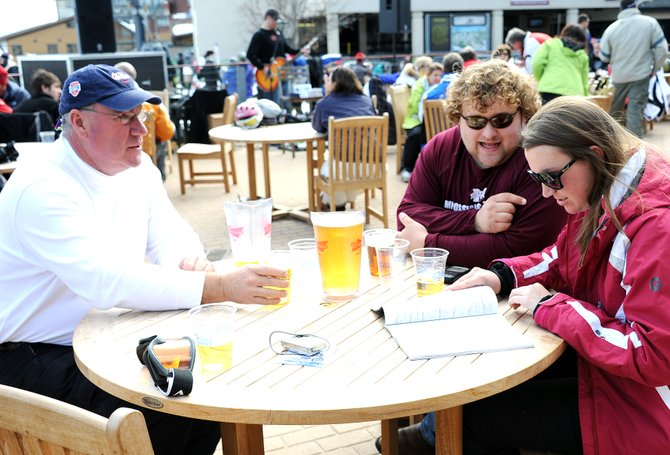 Rusty Stubbs, left, Riley Weaver and Catherine Stubbs plan their day while enjoying some après ski Sunday at the base of Mount Werner in Steamboat Springs.