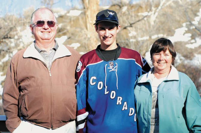 Ethan O'Mailia, middle, stands with his grandfather, David O'Mailia, left, and his grandmother, Shelie O'Mailia, on Sunday outside of their home in Craig. On Friday, Ethan warmed up with the Colorado Avalanche before the team's game at the Pepsi Center.