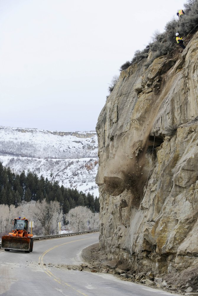 Colorado Department of Transportation worker Jason Simpson knocks off a large loose rock above U.S. Highway 40 between Hayden and Steamboat Springs on Wednesday.