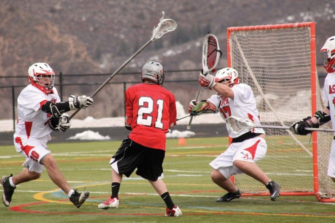 Aspen Skiers' goaltender Daniel Ryerson attempts to block a shot from Steamboat Springs High School's Jackson Coe on Saturday afternoon at Aspen High School. Steamboat won the game, 13-5.