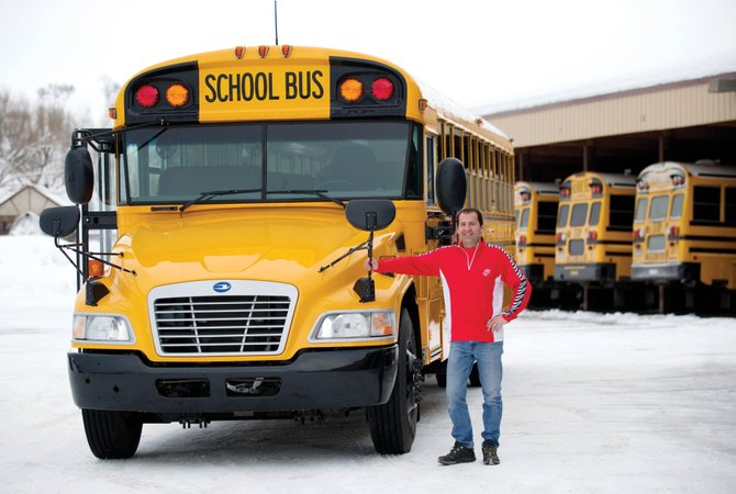 Pascal Ginesta, Steamboat Springs School District's director of maintenance operations and transportation, stands in front of a new bus that uses alternative sources for fuel.