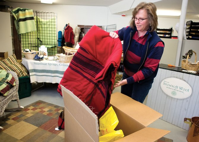 Nancy Mucklow unpacks a wool blanket from a box at the Routt County Woolens store on the campus of Colorado Mountain College in Steamboat Springs. Mucklow was preparing for the stores final sale. Routt County Woolens, which produced and promoted local wool ranchers, has decided to call it quits after 14 years.