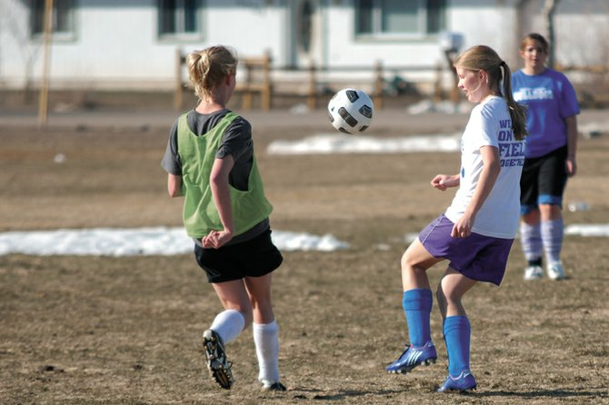 Sophomore Rose Howe, right, looks to get around a defender March 15 during a Moffat County High School girls varsity soccer team practice at Woodbury Sports Complex. The Bulldogs couldn't muster enough offensive firepower Monday to slow Glenwood Springs, dropping the Western Slope League contest, 8-1.