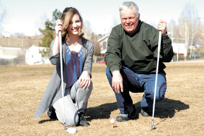 Caitlin Harjes, left, poses with her father, Ken Harjes, on Wednesday outside of Craig Middle School. Caitlin was taught to golf at the age of 5 by Ken and now, as a Moffat County High School freshman, is being coached by one of her father's previous players, Ann Marie Roberts.