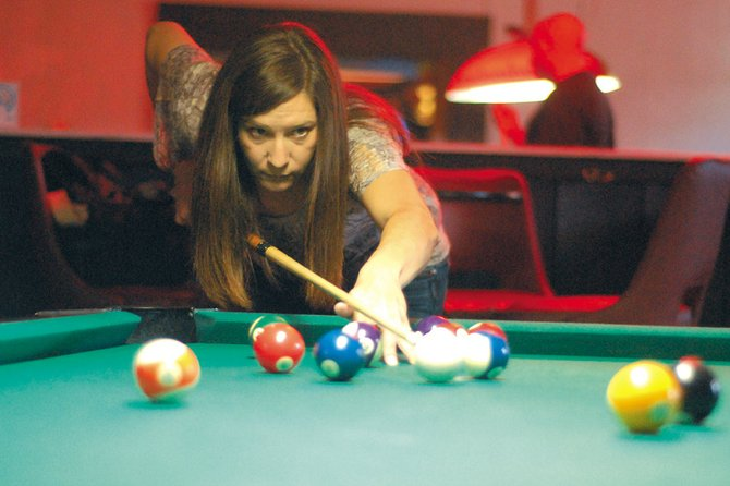 Kim Griffin, 38, practices her technique Wednesday at the Popular Bar. Griffin plays in the Craig Billiards Congress of America pool league, which will be hosting the City Championships on Saturday at the Pop.