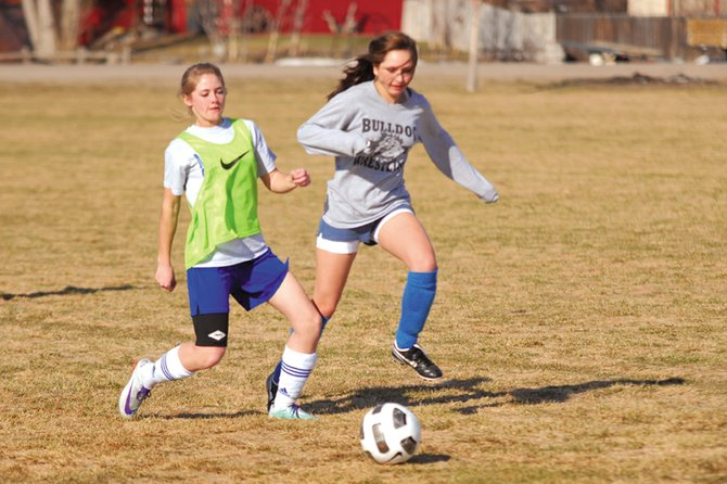 Amanda Brewer, left, a Moffat County High School senior, tries to defend MCHS junior Erika Quenonis during practice March 15 at Woodbury Sports Complex.  The MCHS girls varsity soccer team returns 33 players this year, and will be led by the team's six seniors.