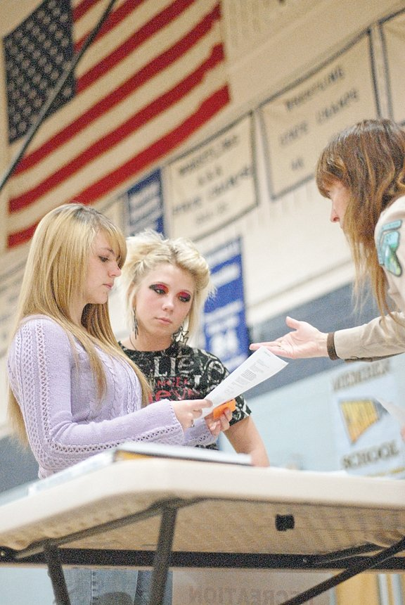 Moffat County High School sophomores Kayla Hall, left, and Karli Griffith, middle, talk to Gina Robison from the Bureau of Land Management's Little Snake Field Office during the school's second Career Day. For three hours Wednesday morning, a wide range of Craig businesses and organizations set up booths in the MCHS gymnasium to talk to students about job opportunities within their respective fields.