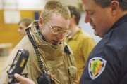 MCHS junior Evan Walters, left, tries on fire gear with the help of Craig Fire/Rescue firefighter Shane Thomas during the school's Career Day.