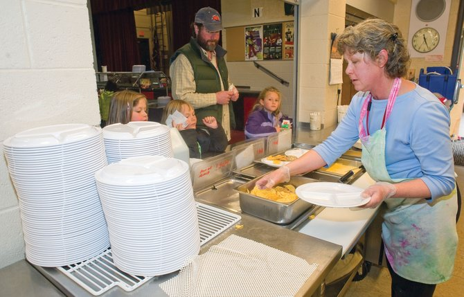Mary Kelley dishes out food at the Strawberry Park Elementary School cafeteria. The school has shifted to using reusable plastic plates instead of Styrofoam plates that were thrown away. It's just one of the many efforts the school has implemented this year as part of programs aimed at sustainability.