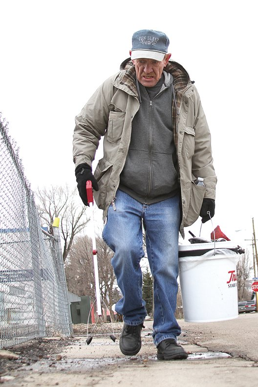 Craig resident Dave Seed, 62, walks Friday near Craig City Park with a five-gallon bucket and a grabber he uses to pick up trash. Seed, now retired, spends his days walking about 10 miles around town and picking up trash. In two years, he lost 112 pounds through walking, which helped improve his health.