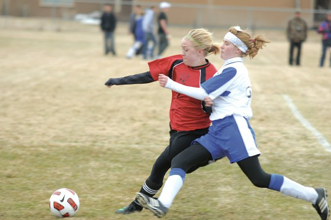 MCHS sophomore Kelsie Pomeroy, right, fights for the ball with a Grand Valley High School defender Friday at Woodbury Sports Complex. Pomeroy scored the go-ahead goal for the Bulldogs in the second half and the team won their first game of the season, 4-1.