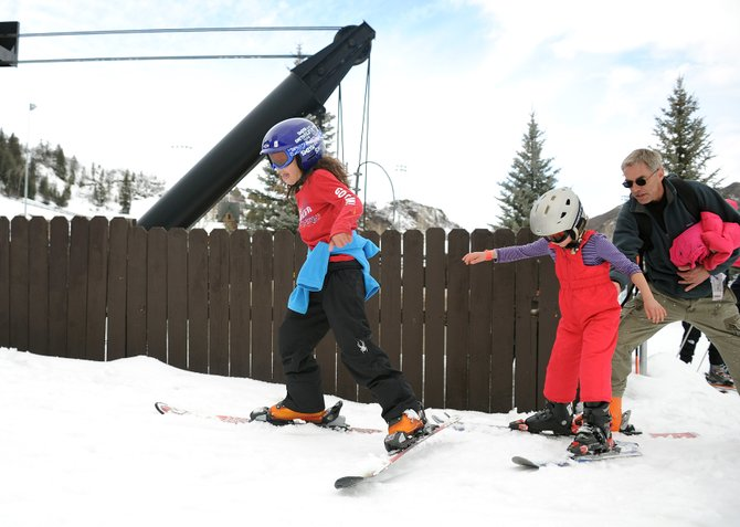 KC Lynch leads the way as Jonathan Schmauder helps Angelina up to the lift at Howelsen Hill on Sunday in Steamboat Springs. Sunday was the last day for skiing at the downtown ski area.