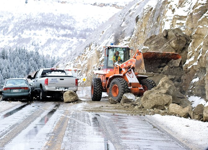 A Colorado Department of Transportation employee removes rocks from U.S. Highway 40 between Steamboat Springs and Hayden after a rockslide closed the road for about two hours Monday morning. Two westbound vehicles were struck by the sliding rocks. No serious injuries were reported.