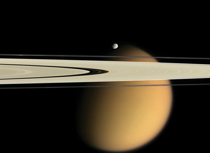 Saturn's giant, smoggy moon Titan looms large behind Saturn's razor-thin rings in this Cassini spacecraft image radioed to Earth in October 2007. The tiny ice-moon Epimetheus seems suspended over the icy rings. Cassini continues to orbit Saturn and return stunning images and data to Earth. Catch Saturn with the unaided eye in spring as it passes closest to Earth in early April.