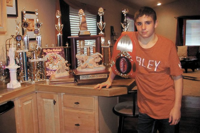 TJ Shelton, a Craig Bad Dogs youth wrestler, poses with his awards in his home in Meeker. Shelton won the Tri-State belt March 12 in Arizona and the Triple Crown and Golden Gear on March 20 in Denver.
