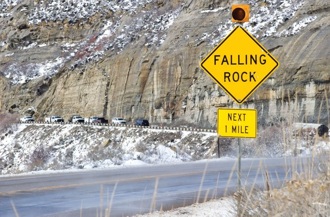 A sign warns drivers entering a canyon east of Hayden to watch for falling rocks. A rockslide in the canyon closed U.S. Highway 40 for two hours Monday, and the Colorado Department of Transportation crews, which can be seen in the background, were still working Tuesday to remove a large boulder that limited traffic to one lane.