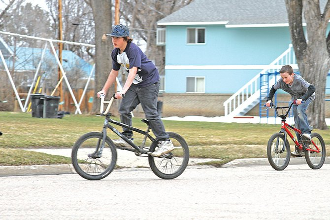 "Caleb Myers, 10, left, leads Gavan Kendall, 11, through a series of practice moves on their bikes Tuesday in front of Breeze Park. The two bikers said they use the edges of the sidewalk to practice their jumps ""every once in a while."" Soon, the park may change ownership from the Moffat County School District to the City of Craig. The proposed land transfer will allow the city to make capital improvements to the park."