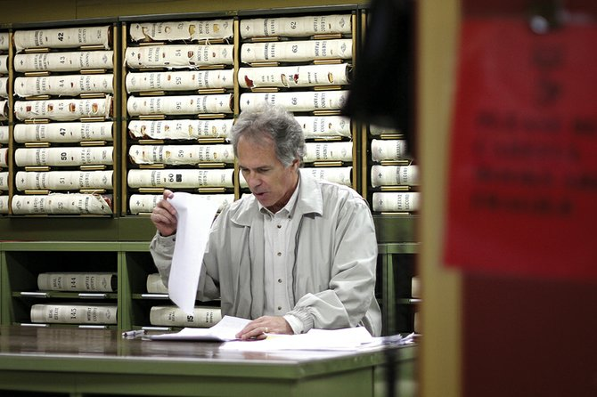 A landman sorts through land and mineral ownership records in the back room of the Moffat County Clerk and Recorder's office in mid-March. Moffat County recently opened sealed bids from a mineral auction on 1,055 acres of minerals, which could net about $1.3 million in revenue for Moffat County's taxing districts. The commission could approve the bids at next week's regular meeting.
