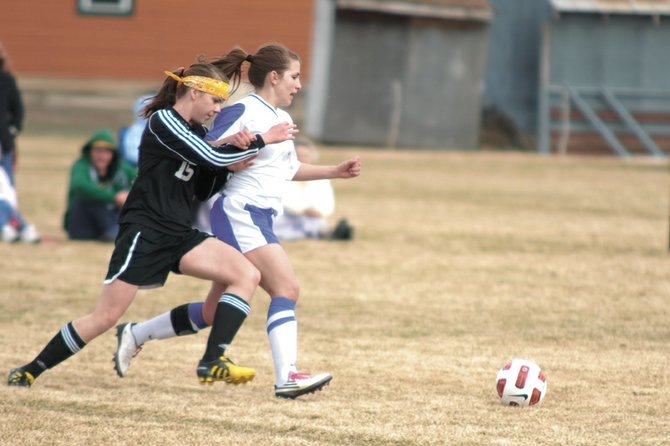 MCHS senior Justine Hathhorn, right, fights with a Battle Mountain defender for the ball Thursday at Woodbury Sports Complex. The Bulldogs were not able to contain the Huskies in the first half and fell 4-1.