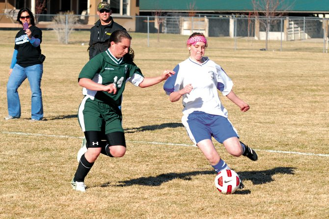 Kelsie Pomeroy, a Moffat County High School sophomore, right, sets up for a kick on goal Friday against Delta High School. The MCHS girls varsity soccer team allowed the Panthers to score a goal late in the game and fell at home, 3-2.