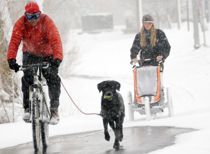 Leighton White and his dog Endo lead the way for Valerie Kutansky and the couple's child, 15-month-old Ayla on Sunday in Steamboat Springs. Seemingly tropical temperatures Saturday had Steamboat residents in shorts and on bicycles, but a late-season snowstorm plunged the town back into winter Sunday.