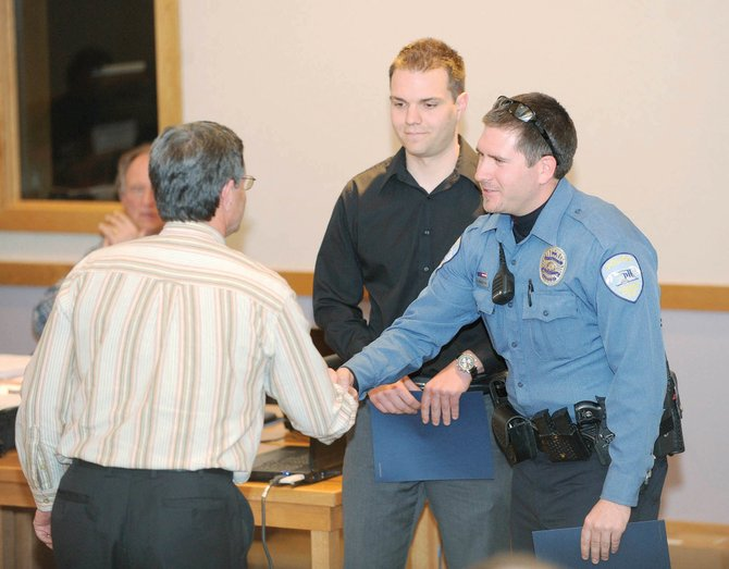 Steamboat Springs Police Department officers Scott Middleton, right, and Matt Conley, middle, are congratulated by Yampa Valley Medical Center CEO Karl Gills after a proclamation was read at Tuesday night's Steamboat Springs City Council meeting to recognize the officers' work related to a Feb. 25 incident at the hospital. Not pictured is officer Stuart Hutton, who also was recognized.