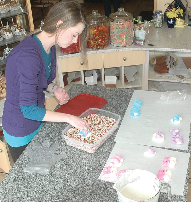 Amanda Gagnebin, of Rocky Mountain Chocolate Factory, dips marshmallow Peeps in white chocolate and sprinkles Friday.