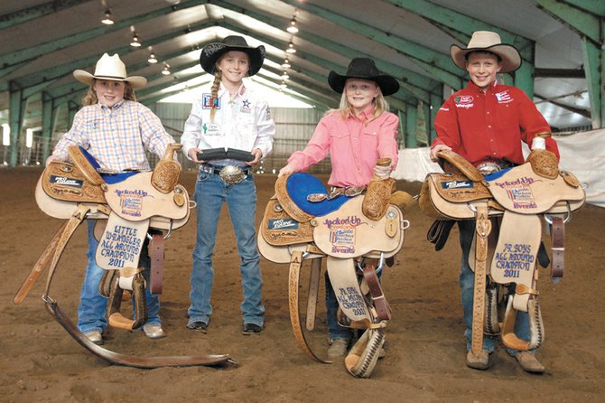 From left, Amber Salazar, Kinlie Brennise, Jaidyn Steele and Kasen Brennise hold their saddle awards Wednesday in the indoor arena at the Moffat County Fairgrounds. Amber, Jaidyn and Kasen took home saddles for winning the all-around points award in their respective age divisions in the Jacked Up Events Little Britches Rodeo Series in Rifle, while Jaidyn won reserve all-around in the junior girls division. Casey Barnes also won a saddle in the senior boys division and Trent Vernon won the reserve all-around in the junior boys division.
