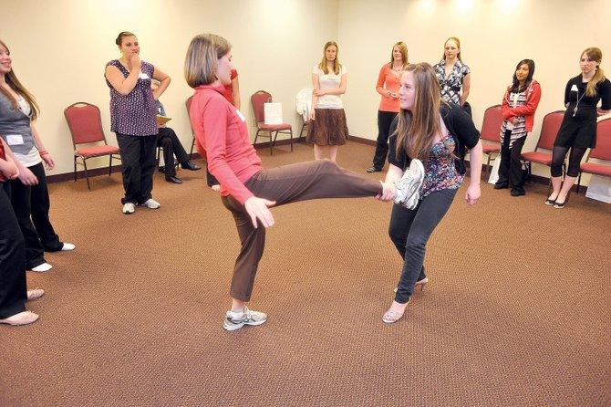 Steamboat Springs middle school student Amber Finch grabs the foot  of instructor Marchele McCarthy during a demonstration  that was part of a self defense class at the 2011 Girls to Women Tuesday at The Steamboat Grand.