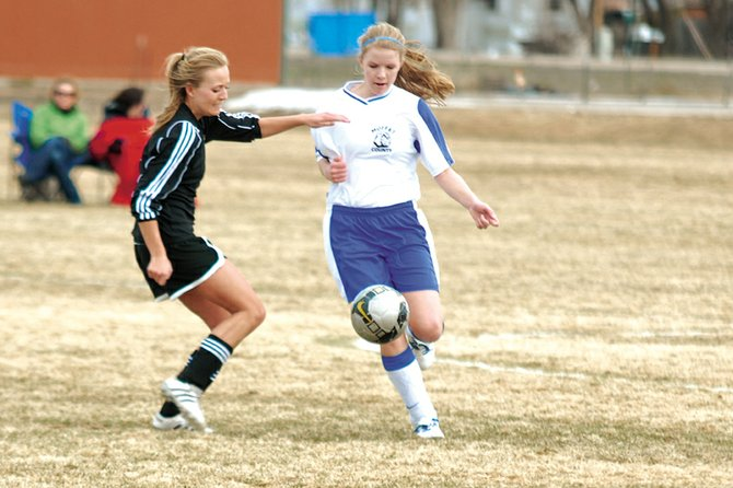 Rose Howe, right, takes the ball from a Battle Mountain High School defender March 31 at Woodbury Sports Complex. The Moffat County High School girls varsity soccer team pushed Palisade to two overtimes Tuesday, but Palisade took advantage of a fortunate bounce to win, 2-1.