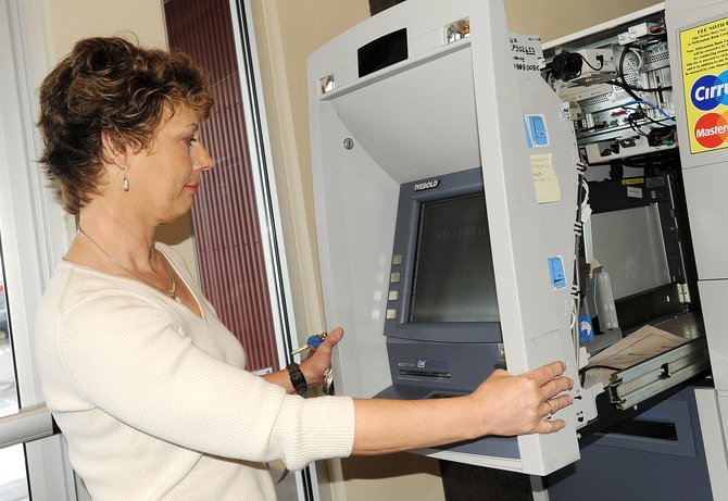 Nina Hanson services an ATM at Millennium Bank in Steamboat Springs. Local bank officials say they are recovering from the financial collapse.