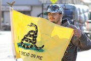 Craig resident Dillon Catt, 19, shows the Gadsden flag to cars passing by Friday at the 2011 Tax Day Freedom Rally hosted by the Bears Ears Tea Party Patriots at the Moffat County Courthouse. The rally was the second of its kind he has attended and he said he was pleased with the turnout.