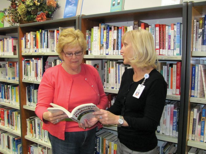SportsMed Office Manager Mary Jones, right, discusses a book on probiotics with Community Health Resource Center researcher Catherine Payne.
