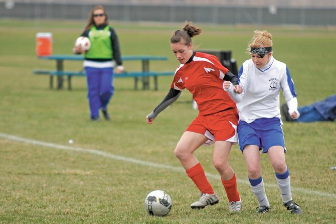 Kelsie Pomeroy, right, struggles with a Glenwood Springs defender Saturday at Woodbury Sports Complex. The Moffat County High School girls varsity soccer team couldn't break through Glenwood's defense and fell 6-0 at home.